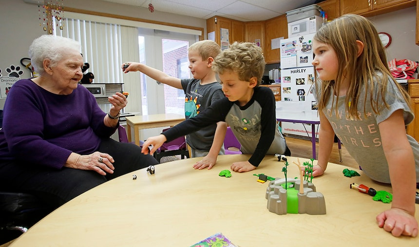 Lorraine Grove, a resident of Elim Care Center in Fargo, plays with (from left) Carter Hins, Danny Mahli and Ivy Hedlund.